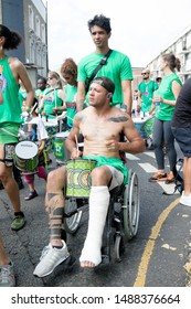 London, United Kingdom, August 25th 2019:-A shirtless samba drummer in a wheel chair at the Notting Hill Carnival in West London, the Notting Hill Carnival is Europe's largest street party.