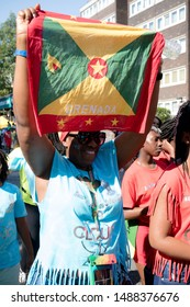 London, United Kingdom, August 25th 2019:-A  reveller with the flag of Grenada at the Notting Hill Carnival in West London, the Notting Hill Carnival is Europe's largest street party.