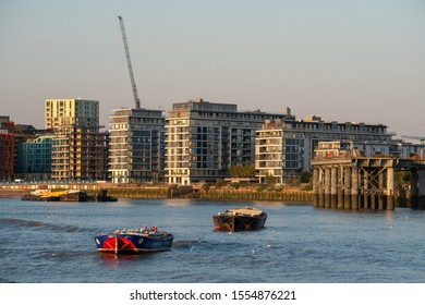 London / United Kingdom - August 26th 2019: Skyline of new riverside apartment buildings with boats floating on the river Thames near Greenwich, London, United Kingdom