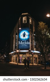 London, United Kingdom - August 31, 2019: Illuminated facade of Cambirdge Theatre located on Seven Dials, London, showing Matilda musical, at night, people walking in front, selective focus.