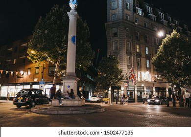 London, United Kingdom - August 31, 2019: People relaxing by Sundial Pillar and walking around Seven Dials, Covent Garden, one of the most popular tourist areas in London, at night.
