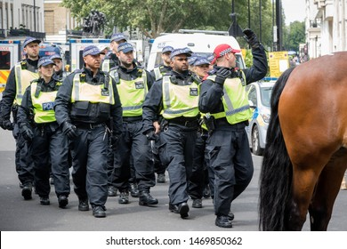 London, United Kingdom, August 3rd 2019:- Police run to form a line across a street in London to prevent Tommy Robinson supporters and anti facist demonstrators clashing