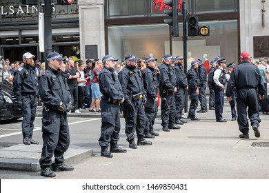 London, United Kingdom, August 3rd 2019:- Police form a line across Regent's street in London to prevent Tommy Robinson supporters and anti facist demonstrators clashing