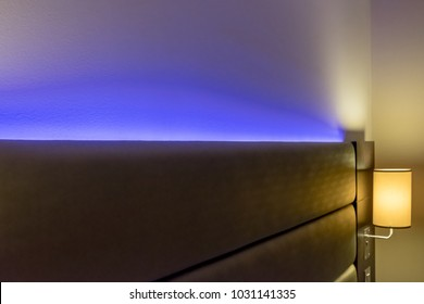 London, United Kingdom - Circa February 2018: Shallow focus of modern LED ambient mood lighting seen in a modern apartment bedroom. An out of focus reading lamp is lit in the background.