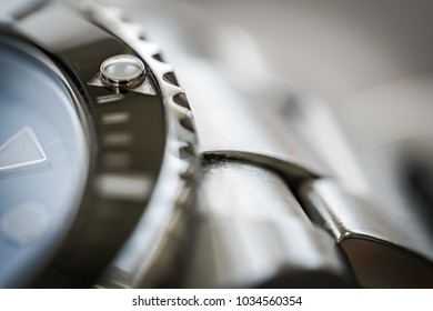 London, United Kingdom - Circa February 2018; Extreme close-up of the rotating bezel and hour marker seen on an iconic, swiss-made divers watch. Part of the watch crystal and steel links are visible.