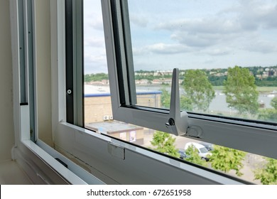 LONDON, UNITED KINGDOM - CIRCA JULY 2017: Close-up view of an opened, double glazed window seen in a private apartment, looking out to further buildings and the River Thames in the distance.