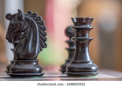 London, United Kingdom - Circa March 2018: Close-up, detailed image of hand carved wooden chess pieces including a knight and rook seen at the start of a chess tournament on a wooden board.