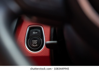 London, United Kingdom - Circa May 2018: Close-up, isolated image of an engine Start Stop button seen on the dashboard of a german manufactured sports car, also showing its part red leather.