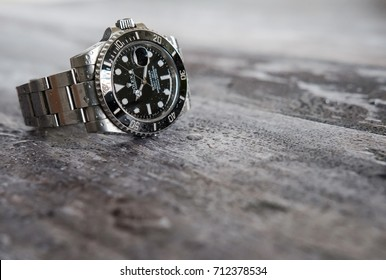 LONDON, UNITED KINGDOM - CIRCA SEPTEMBER 2017: Shallow depth of view of a famous, Swiss manufactured men's divers watch seen having just been taken off by a diver, seen on some wooden decking.
