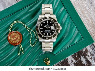 LONDON, UNITED KINGDOM - CIRCA SEPTEMBER 2017: Detailed view of a well-known Swiss manufactured men's divers timepiece seen on top of its green presentation case with a seal pendant.