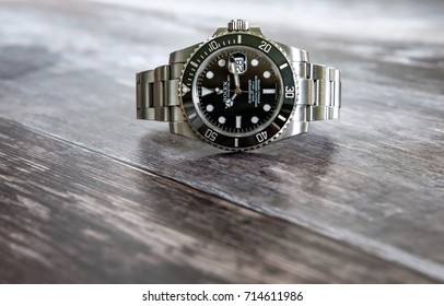 LONDON, UNITED KINGDOM - CIRCA SEPTEMBER 2017: Full face view of a famous, Swiss manufactured men's divers watch seen placed on top of a wooden surface, showing the date window also.