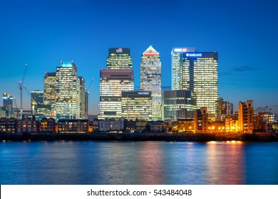 London, United Kingdom - December 22, 2016: Panoramic view across river Thames to skyscrapers district Canary Wharf in London at dusk.