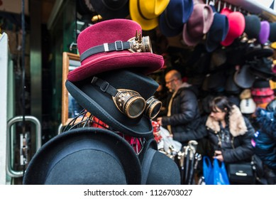 London, United Kingdom  - December 31, 2017: Hats and Gothic black sunglasses with diffracted lens or Kaleidoscope in a fashion shop of Camden Lock Market in London, England, United Kingdom