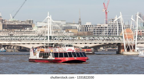 London, United Kingdom - Februari 21, 2019: A City cruises touristic boat navigating by Thames river with a lot of tourists on it, in London, UK