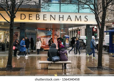 London, United Kingdom - February 01, 2019: People in front of Debenhams store Oxford Street branch on a rainy day. British multinational retailer was formed in 1778.