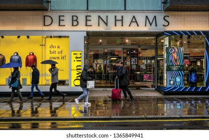 London, United Kingdom - February 01, 2019: People walks in front of Debenhams store Oxford Street branch on a rainy day. British multinational retailer was formed in 1778.