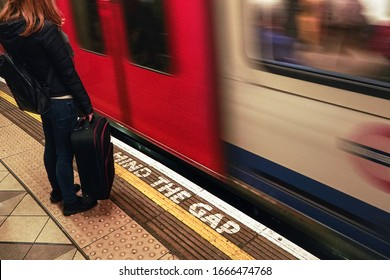 London, United Kingdom - February 01, 2019: Girl with her black suitcase waiting at London underground station, as train is arriving behind yellow line with Mind the Gap warning