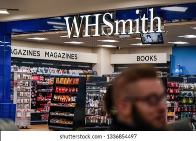 London, United Kingdom - February 05, 2019: Unknown man walks in front of WHSmith branch at London Luton airport. WHS is major British retailer selling mostly books, stationery, magazines & newspapers
