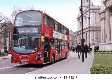 LONDON, UNITED KINGDOM - FEBRUARY 10: Famous TFL red bus on a stop near Millennium bridge with people walking by in London, UK - February 10, 2015; Traditional red London bus with open front door.