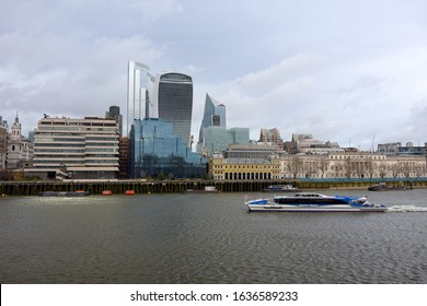 London/ United Kingdom - February 2 2020 : Looking North at the London skyline complete with a Thames Clipper ferry boat on the river