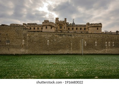LONDON, UNITED KINGDOM - FEBRUARY 2021 - Tower of London, green grass covered with snow, cloudy sky