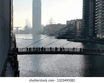 London, United Kingdom - February 26, 2019: Commuters walking across a bridge between Canary Wharf and South Quay in Docklands, Isle of Dogs.