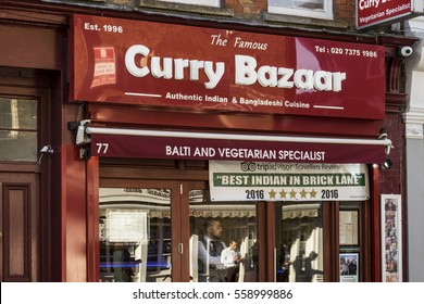 LONDON, UNITED KINGDOM - JANUARY 17, 2017: Exterior of restaurant specializing in Indian and Bangladeshi food in Brick Lane with TripAdvisor sign. Man looking out from behind closed glass door.