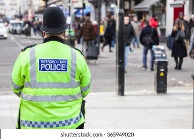 LONDON, UNITED KINGDOM - JANUARY, 2016: Policeman watching people on streets of London