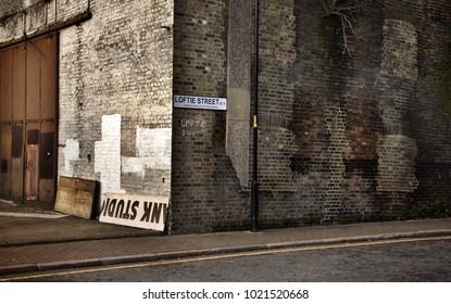 London, United Kingdom - January 27th, 2007: Vintage look corner of Loftie street in Southwark with dirty old brick wall.