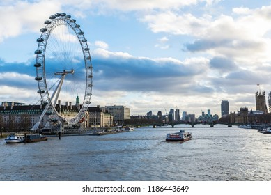 London, United Kingdom - January 4, 2018: Ferris wheel called The London Eye with boats sailing on the River Thames in London, England, United Kingdom