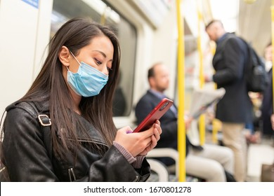 LONDON, UNITED KINGDOM - JANUARY28, 2020: Chinese woman wearing a face mask while travelling by tube to protect from coronavirus.