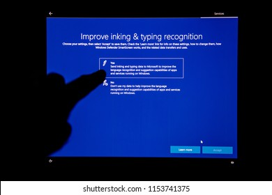 LONDON, UNITED KINGDOM - JUL 23, 2018: Hand interacting on digital touchscreen after Microsoft Windows Update installation - improve inking and typing on laptop