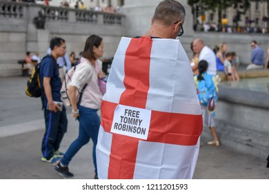 "London / United Kingdom - July 14 2018: far-right protest for former English defence league leader Tommy Robinson. Back of white male draped in  England flag with a sign saying ""free Tommy Robinson"""
