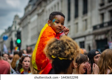 LONDON, UNITED KINGDOM - JULY 2019: Child covered with a rainbow flag sits on a piggyback during a pride parade in London