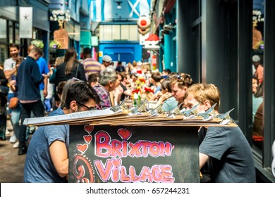 London, United Kingdom - June 10, 2017: Brixton Village and Brixton Station Road Market. Colorful and multicultural community market run by local traders in South London. People in a restaurant