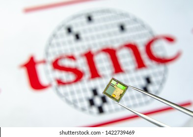 London / United Kingdom - June 12 2019: Close up photo of microchip (aka semiconductor chip, semiconductor device, Integrated Circuit) hold in tweezers with TSMC logo on a background.