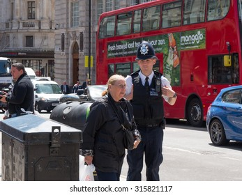 London, United Kingdom - June 15, 2015: British policeman on patrol in Piccadilly Circus from information to a person.
