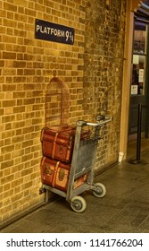 London, United Kingdom, June 2018. Platform 9 and 3/4 at Kings Cross Station, London. A trolly stuck in the wall where fans emulate the Harry Potter adventures. A service assistant for the photo.