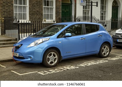 London, United Kingdom, June 2018. A Nissan Leaf parked in the historic center of London. The parking lot is reserved for electric vehicles and is equipped with a quick charging column.