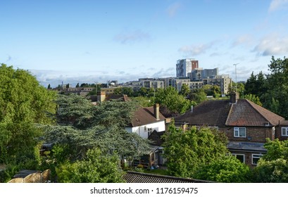 London, United Kingdom, June 2018. London suburbs, Colindale. Typical London houses in red brick and white finishes. On the back we find a small garden, and some low buildings for residential use.