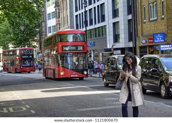 London, United Kingdom, June 2018. Two red double-decker buses, a woman travels across the street while checking her smartphone.