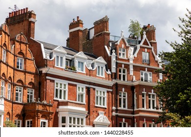 LONDON, UNITED KINGDOM - JUNE 2019: Facade of opulent British Victorian Edwardian terraced flat in red bricks in Chelsea, London.