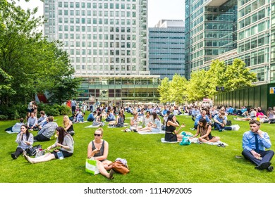 London, United Kingdom - June 21, 2017. Canary Wharf office workers sitting outside and enjoying hot weather and sunshine.