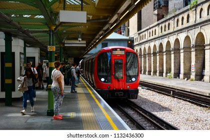London / United Kingdom — June 21, 2018: a S Stock train of District line approaches South Kensington station of London Underground