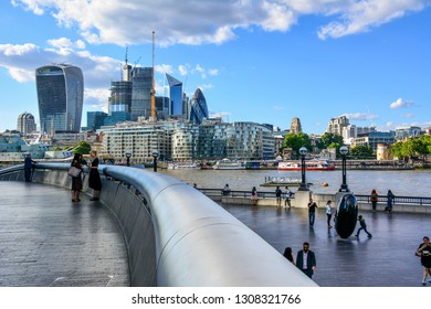 London / United Kingdom — June 21, 2018: the modern South Bank of the River Thames in Southwark, London, with the skyscrapers located in the City of London, a business district