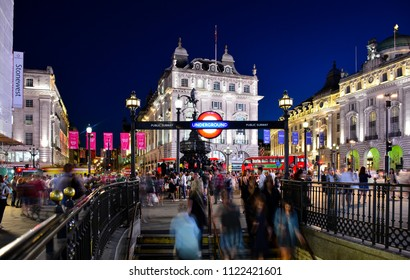 London / United Kingdom — June 28, 2018: view of lively Piccadilly Circus in the evening with the entrance to the underground station and the Shaftesbury Memorial Fountain, known as Eros