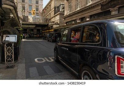 London / United Kingdom - June 28 2019: Entrance to the Savoy hotel with a taxi passing through