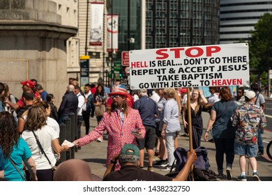 London / United Kingdom - June 28 2019: Man holding religious placard on Westminster Bridge on a sunny day with many tourists passing by