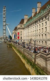 London / United Kingdom - June 28 2019: Side view of the London Eye, Millennium Wheel. County Hall and the Queens Walk with tourists on a sunny day