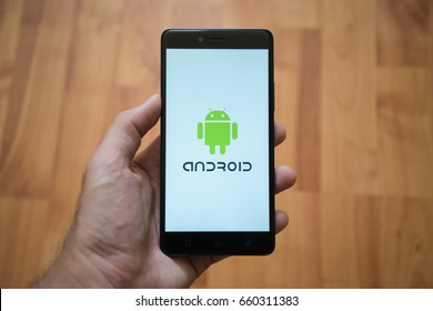 London, United Kingdom, june 5, 2017: Man holding smartphone with Android logo on the screen. Laminate wood background.